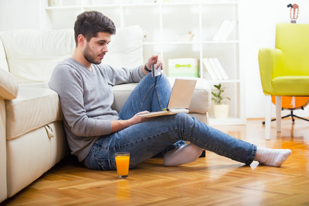 credit card bills: Man holding credit card and using laptop for online shopping - indoors Stock Photo
