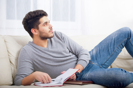 handsome guy: Handsome young man at home writing on notebook, sitting on couch Stock Photo