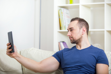 taking video: Young attractive 30s man taking selfie picture or self video with digital tablet at home Stock Photo