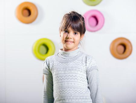 little girl posing: The little girl posing in a playroom