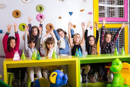Group of happy preschoolers dancing in playroom