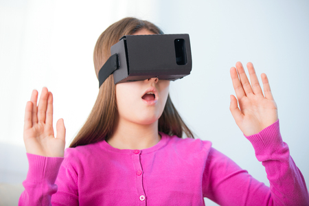 gesticulating: Happy smiling young beautiful young girl getting experience using VR-headset glasses of virtual reality at home much gesticulating hands