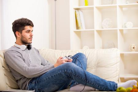 visage homme: Jeune homme appr�ciant jeu d'ordinateur, en jouant avec joystick, sourire