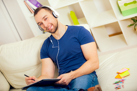 one room school house: Handsome young man at home writing on notebook, sitting on couch, listen to music