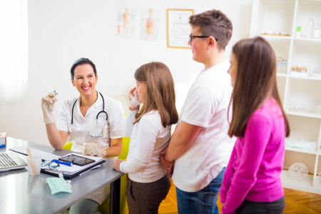 10 12: Female doctor and patient teenagers .Vaccination. Medical examination. Stock Photo