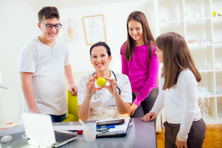 10 12: Female doctor nutritionist and patient teenagers.Doctor holding an apple. Medical examination.