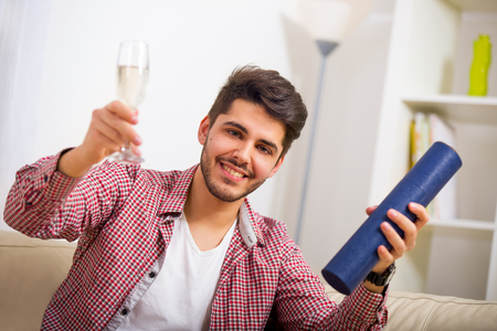 one room school house: Young man sitting on the sofa and holding in his hand university degree, toasts Stock Photo