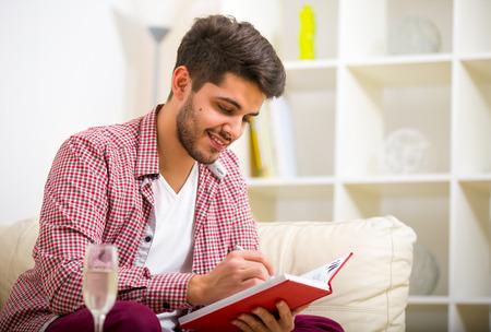 bel homme: Beau jeune homme à la maison écriture sur ordinateur portable, assis sur le divan