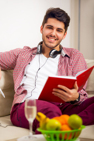 one room school house: Handsome young man at home writing on notebook, sitting on couch Stock Photo