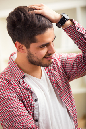 through: Portrait of a Handsome Young Man. The young man passing his hands through his hair