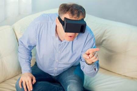 gesticulating: Man getting experience using VR-headset glasses of virtual reality at home much gesticulating hands