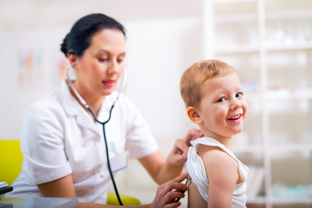 stethoscope boy: Happy little boy at the doctor for a checkup - being examined with a stethoscope
