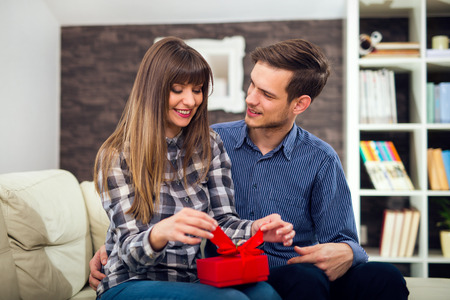 gifting: Young woman is happy and surprised with a gift from her husband, boyfriend.