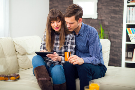 20 to 25 years old: Young couple shopping on internet with tablet