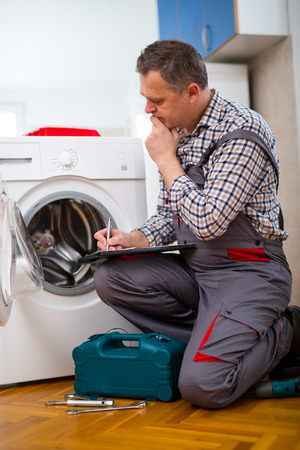 malfunction: Repairman is repairing a washing machine on the white background. Entering malfunction Stock Photo
