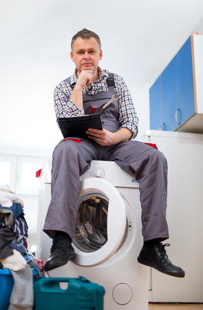 malfunction: Repairman is repairing a washing machine on the white background. Entering malfunction sitting on washing machine.