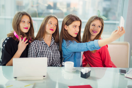 occurrence: Portrait of four young women sitting at the table in the cafe take selfie with smart phone, selective focus