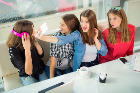 occurrence: Portrait of four young women sitting at the table in the cafe take selfie with smart phone Stock Photo