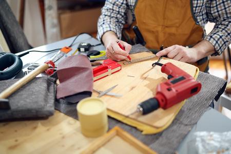 Man upholstering chair in his workshop, measure
