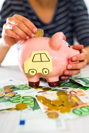women's hand: Saving concept. Womens hand puts money in piggy bank. Selective focus. Saving for a car