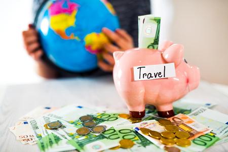 banco dinero: Saving concept. Piggy bank with an inscription travel. Woman holding a globe. Selective focus. Foto de archivo
