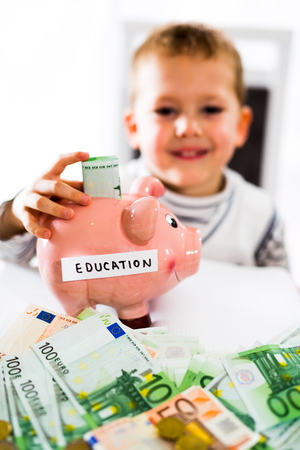financial education: Saving concept. Child puts money in piggy bank. Selective focus. Saving for a education