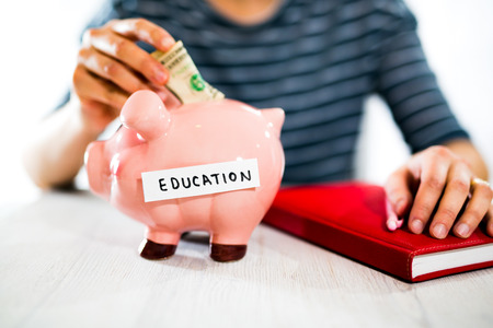 women's hand: Saving concept. Womens hand puts money in piggy bank. Selective focus. Saving for a education Stock Photo