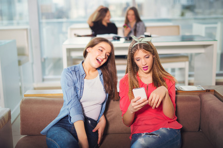 occurrence: Portrait ofteenager girls sitting at the table in the cafe, selective focus Stock Photo
