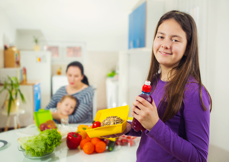 school teens: Mother making breakfast for her children in the morning and a snack for school at home. The girl with a box for a snack in the kitchen