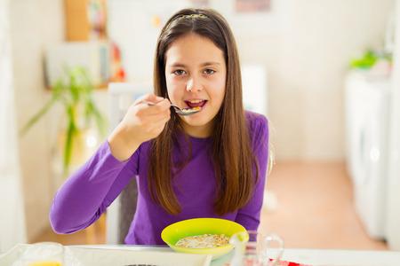 comiendo cereal: Ni�a comiendo cereales en la cocina