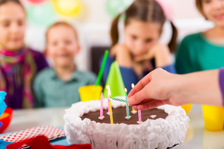 gateau anniversaire: Enfant sur la fête d'anniversaire préparé soufflant les bougies sur le gâteau