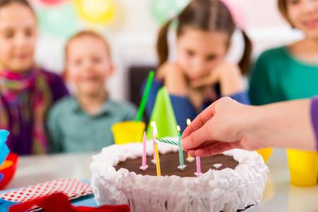 torta de cumpleaños: Niño en la fiesta de cumpleaños preparada soplando las velas en la torta