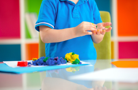 nurser: Child moulds from plasticine on table. hands with plasticine.