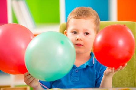 ballons: Joyful kid boy on birthday party holding ballons
