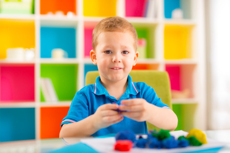 nurser: Cute  boy moulds from plasticine on table
