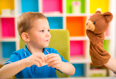 only 3 people: Young boy playing with teddy bear at home
