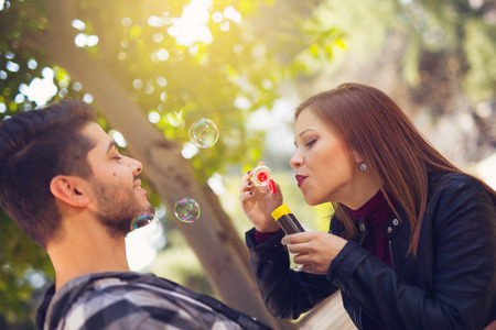blower: Couple Relaxing in the Park with bubble blower. Spring time.