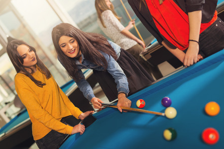Billiards game. Group of friends playing pool together.