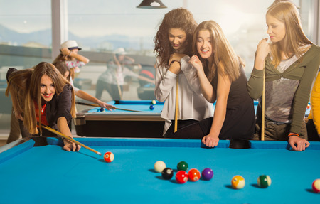 billiards rooms: Billiards game. Group of friends playing pool together.