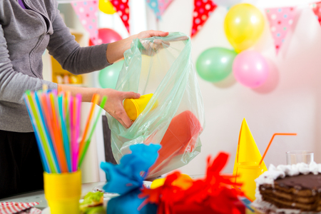 mess: Woman cleans  mess after the childrens birthday Stock Photo