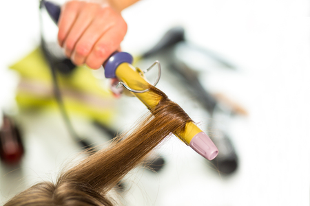 coiffeur: Hairdresser curling woman hair with electric iron curler tong.
