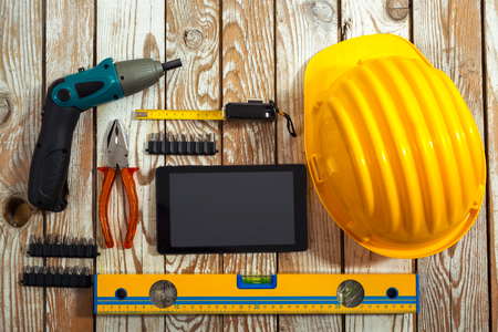 wooden work: Helmet, tablet and work tools on a wooden background