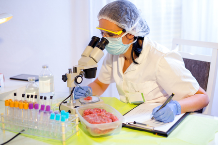 Food quality control expert inspecting at meat specimen in the laboratory. Selective focus Stock Photo