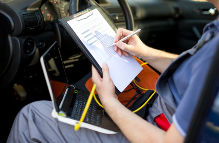 Mechanic writing on clipboard, sitting in the car, close up Stock Photo