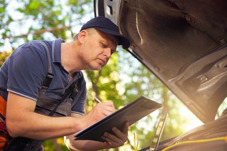 mot: Portrait of a mechanic at work writing on clipboard