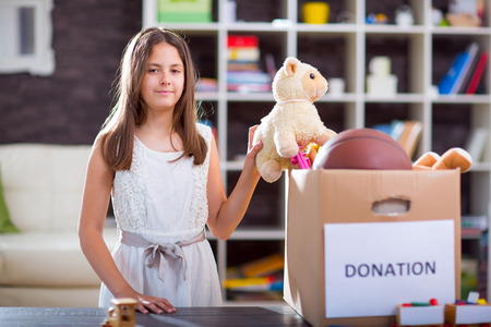 Meisje dat donatie doos vol met spullen te doneren Stockfoto
