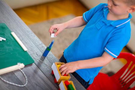 one room school house: Little boy writes by blackboard at home
