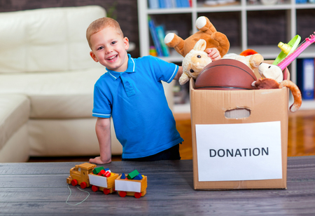 Boy taking donation box full with stuff for donate