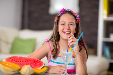kindergartner: Summer refreshment.The girl drinking lemonade in front of her was watermelon and melon