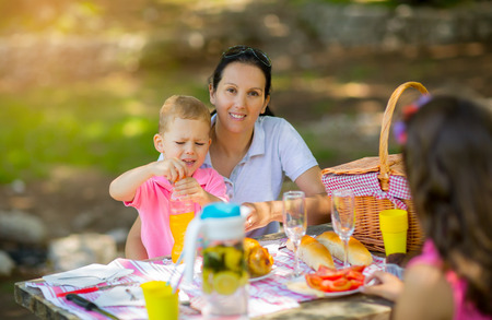 mother on bench: Mother with children enjoying on picnic sitting on a bench Stock Photo